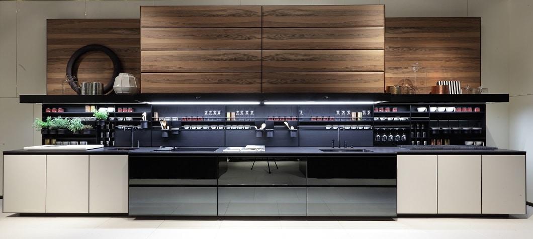 Der italienische Küchenhersteller Varenna lässt mit den großen Walnussfronten seiner Oberschränke das Küchengeschirr per Touch verschwinden. (Foto: Varenna)