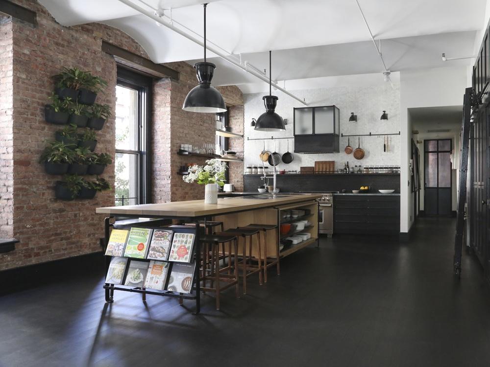 Dunkles Interior Beim Industrial Design, Das Aufgepeppt Wird Durch Hellen  Backstein, Die Holzarbeitsplatte Und Vor Allem Eine Grüne Bepflanzung.