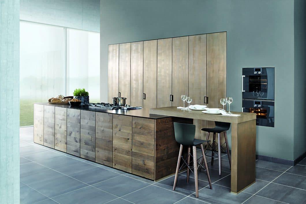 Es muss nicht immer eine verlängerte Arbeitsplatte sein: Auf die Kücheninsel lässt sich auch problemlos ein höherer Bar-Aufsatz als Tisch montieren. (Foto: Zeyko, Forum Moor Eiche)