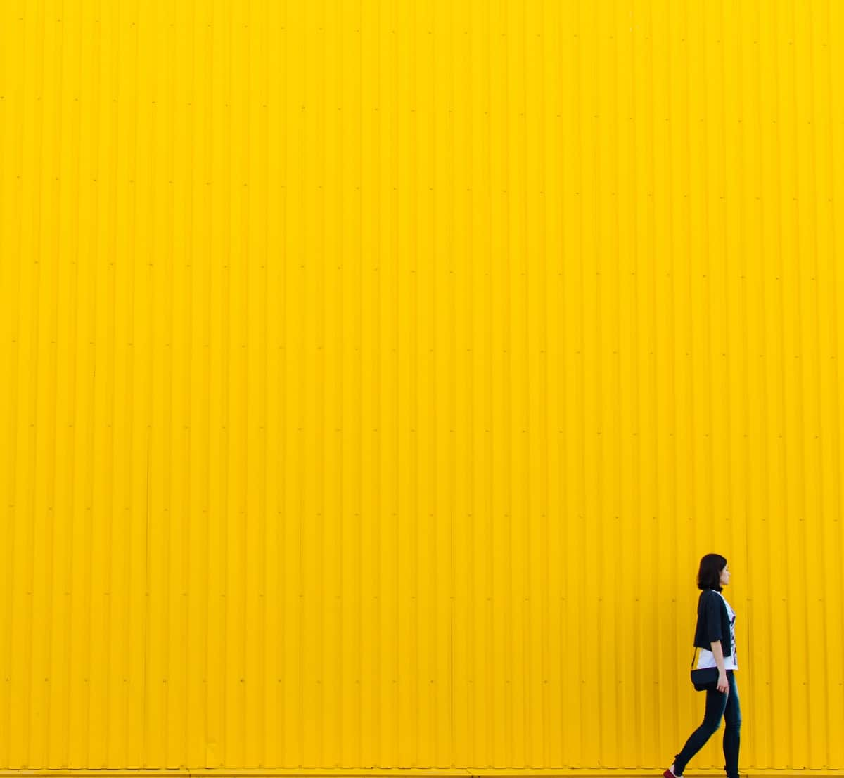 Rodion Kutsaev yellow wall, woman walking by