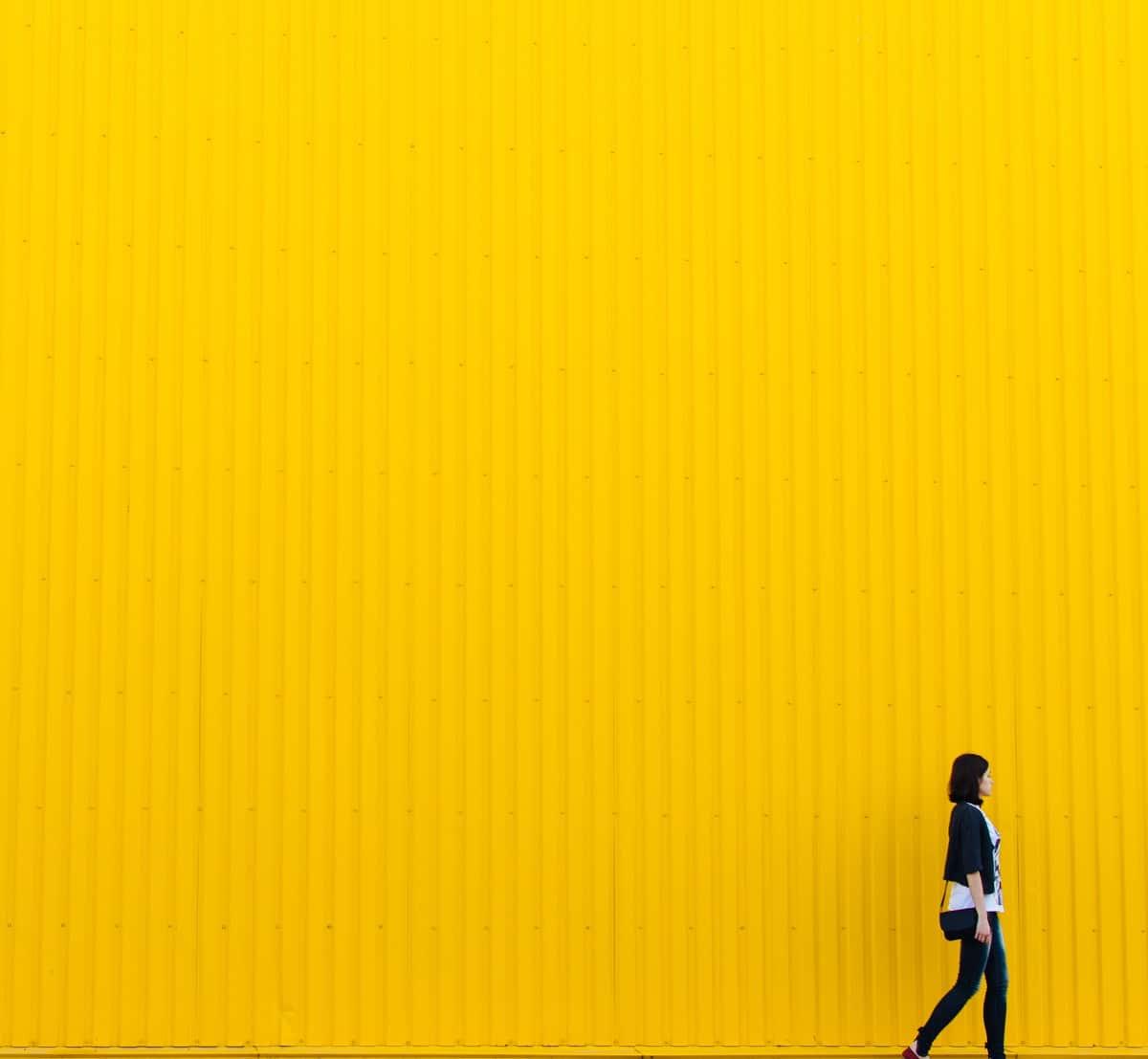 Rodion Kutsaev yellow wall, woman walking by
