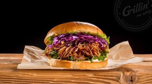 """Der """"King of Queens Burger"""" mit 8h gesmoktem Pulled Pork, Tequila-Cole Slaw, Limette, roten Zwiebeln, Jalapenos, Salat und einer feurigen BBQ-Sauce auf einem gegrillten Brioche Bun. Wer da nicht schwach wird, ist selber schuld (P.S.: Es gibt auch einen Burger mit Veggie-Tandoori-Patty). (Foto: grillin.me)"""