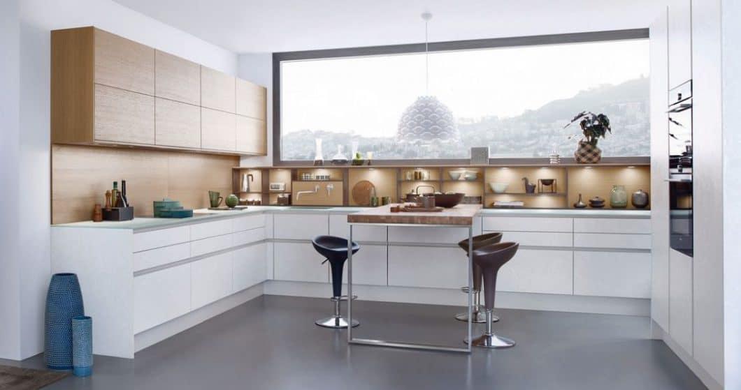 Gleiches Prinzip bei Leicht: Die Küchentisch-Platte spiegelt die Farbe der Küchenfronten wider, nimmt sich aber ansonsten mit einer robusten Holzfläche auf grazil designten Edelstahlfüßen zurück - und ist doch im Mittelpunkt des Geschehens. (Foto: Leicht)