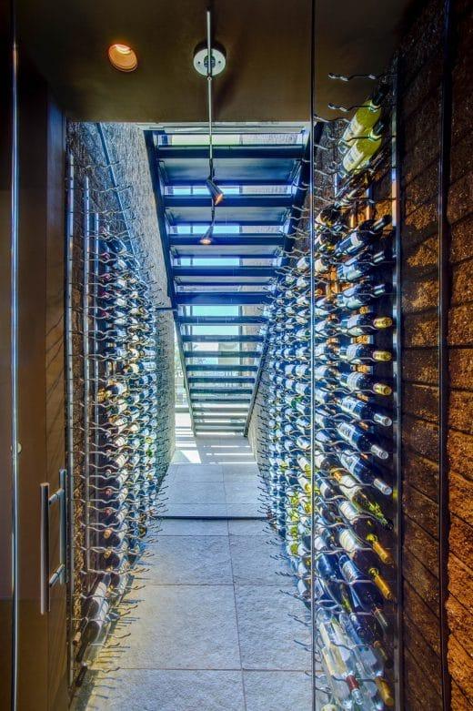Auch in einer kleineren Wohnung findet sich unter der Treppe ungenutzter Stauraum - warum nicht für futuristisch beleuchtete Weinregale nutzen? Kühl bleibt es dort auch. (Architekten: Kevin Howard Architects)