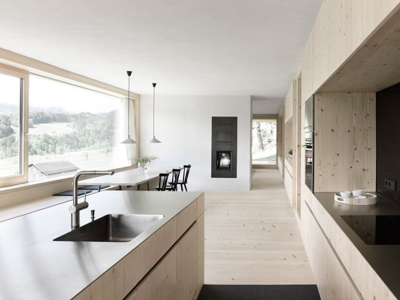 Küchenschränke, Kochinsel und Fußboden sind aus hellem Fichtenholz gebaut und gehen fließend in einander über. Die dunklen Arbeitsplatten und die schwarzen kleinen Fliesen der Rückwand setzen sich stringent dagegen ab. (Foto: Adolf Bereuter)