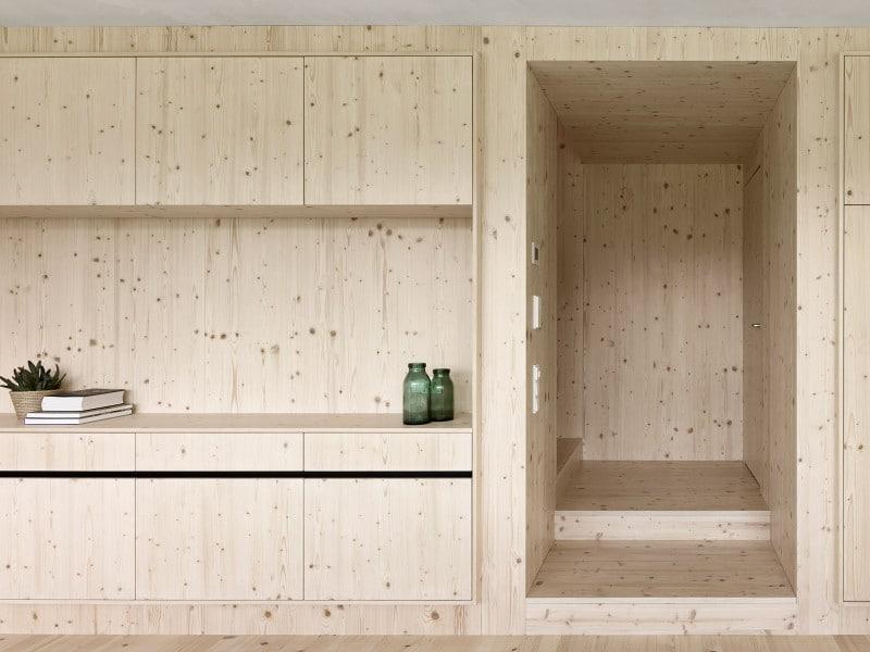 Die längliche Wand aus Fichtenholz dominiert die Räumlichkeiten einerseits, nimmt sich andererseits zurück und lässt Auffälligkeiten wie Schränke, Nischen oder Türen nur im gleichen Farbton zu. (Foto: Adolf Bereuter)