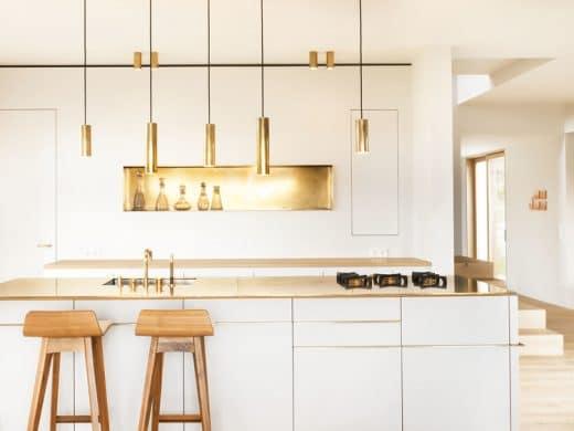 Die Küche ist ein atmosphärisch gelungener Mix aus edlen Messing-Applikationen, hellen, freundlichen Holzelementen und gedeckten Weißtönen. (Foto: spandriwiedemann.de)
