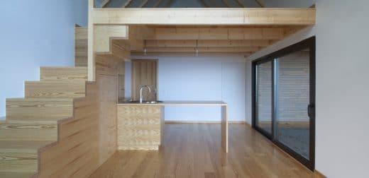 Die Küche ist minimalistisch-schlicht an das sehr helle Kiefernholz der Treppe und Dachbalken angepasst - und bietet einen spektakulären Ausblick. (Foto: dirkmayer.com)