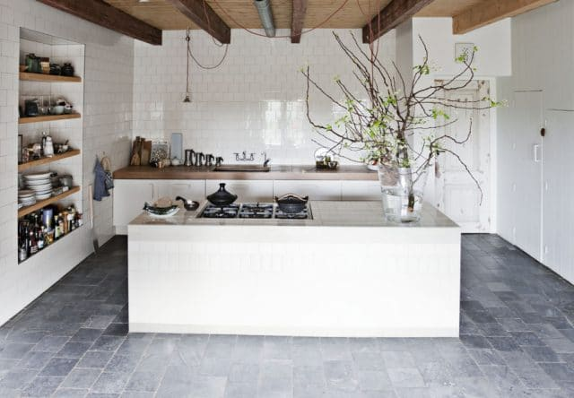 Die weiße Küche wirkt im Kontrast zu ihrer Vorgeschichte besonders rein und aufgeräumt, erinnert aber dank rustikaler Fliesen und warmer Holzelemente an die bäuerische Idylle. (Foto: ina-matt.com)