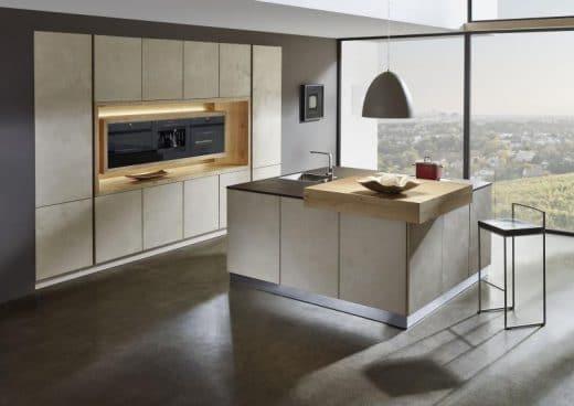 Geräte werden in die Küchenwand montiert, Spülbecken unsichtbar in der Kochinsel versenkt. Ein Aufsatz am Küchentresen dient als Schneidebar und Bar-Tisch, an dem schnelle Mahlzeiten eingenommen werden können. (hier: Sachsenkuechen, neue Natursteinoberflächen, Ausblick auf Living Kitchen 2017)