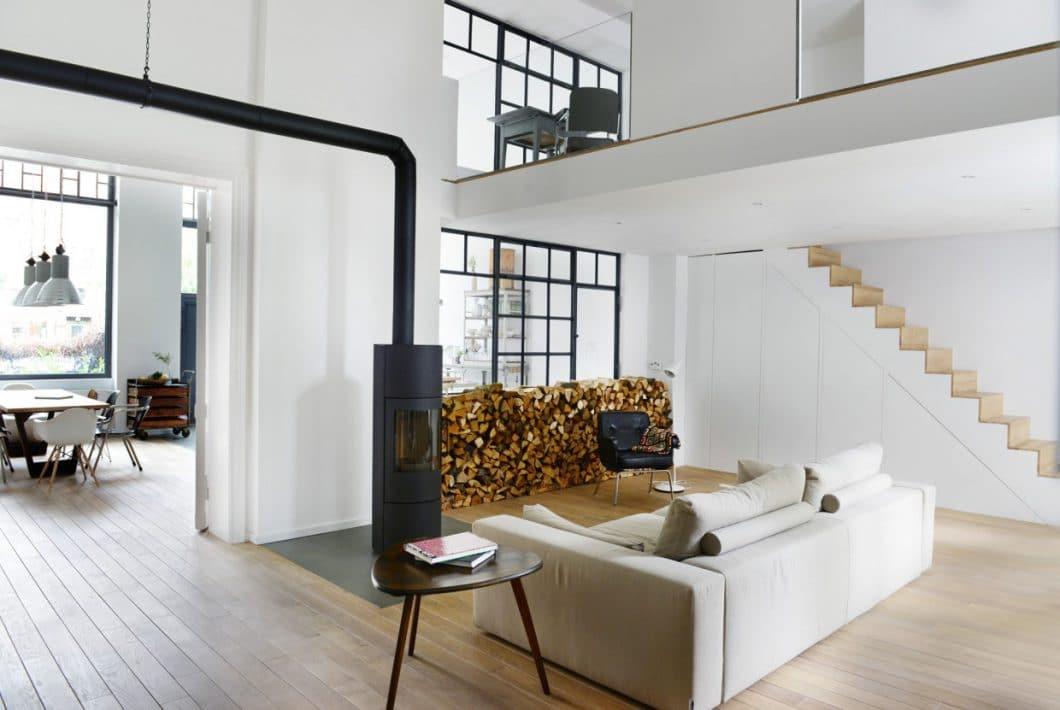 Auch im wohnzimmer wird der industrial style mit einem stahlofen sowie stahl fensterrahmen weitergeführt