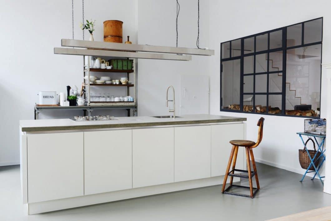 Der küchenboden aus estrich grenzt den freistehenden küchenblock vom direkt gegenüberliegenden esstisch ab der grau