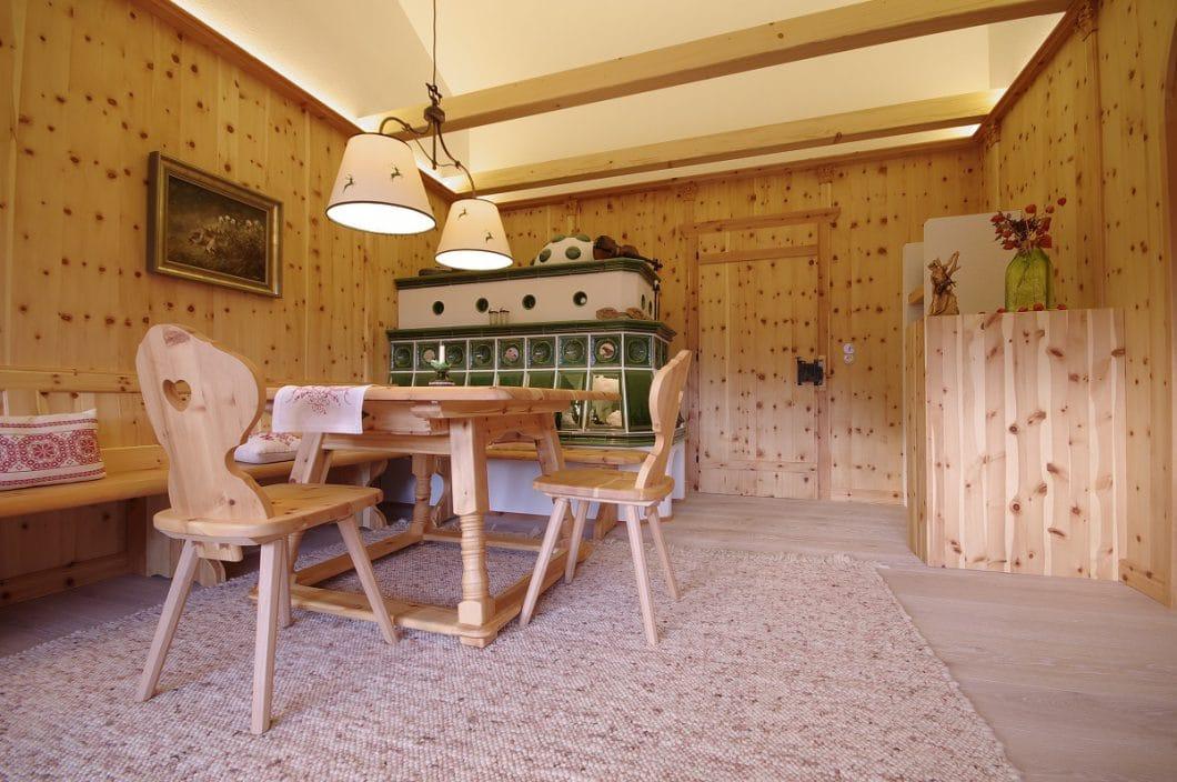 Der Sitzplatz um Essecke und Kamin herum ist wieder sehr traditionell in hellen Holzfarben gehalten. Foto: Grill & Ronacher