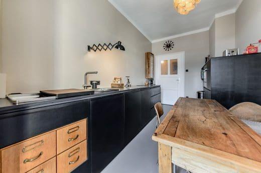 Scherenleuchte, ein antiker Holztisch und der honigfarbene Flohmarktfund - alte Schubladen - verleihen der modernen Küche ein industrielles Flair. (Foto: Ludwig 6)