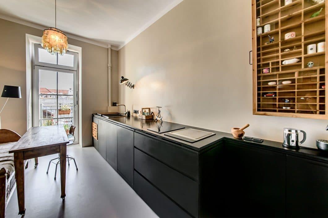 Da der schwarze Küchenblock sehr mächtig wirkt, wünschte die Besitzerin keine Oberschränke und keinen sichtbaren Spritzschutz über dem Kochfeld. Die Lösung: Abwaschbare Keramikfarbe. (Foto: Ludwig 6)