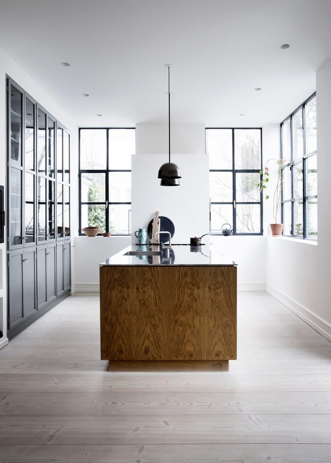 Warmes Holz, eine dünne Granitarbeitsplatte und eine blaugraue Mattlackfront definieren diese dänische Küche im skandinavisch-zurückhaltenden Stil. (Foto: Line Thit Klein)