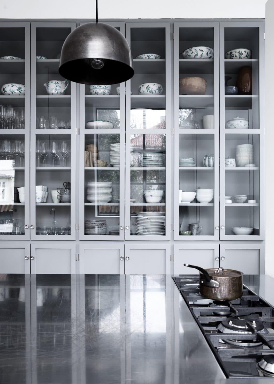 Kleine Eigenheiten, für die wir die Dänen lieben: Atelierfenster, die das Küchengeschirr zur Geltung bringen. Und ungewöhnlich angebrachte Kochfelder, von beiden Seiten zugänglich. (Foto: Line Thit Klein)
