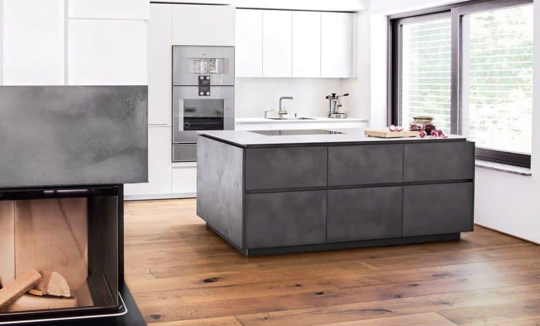 """""""Statement eines Kochs"""" heißt diese betörend minimalistische, moderne Küche aus gespachteltem Beton: Sie passt damit perfekt zum Eichenholzboden und der glatten, weißen Küchenwand. Fronten: Lack Feinstruktur weiß; Kücheninsel: Holzwerkstoffplatte mit Betonspachtel; Arbeitsplatte: Edelstahl 5mm, warmgewalzt (Foto: Selektion D, Lang Küchen & Accessoires)"""