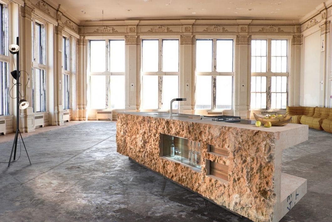 Eine Marmorküche, die aus einem einzigen Felsstück herausgesprengt wurde. Als Kontrast dazu: Warme Schubladen aus Nussholz. (Foto: werkhaus)
