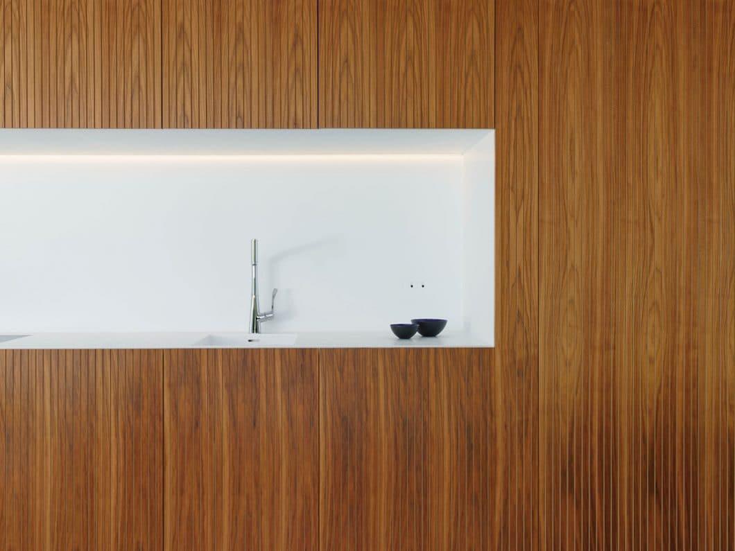 Eine fugenlose weiße Küchenrückwand inklusive Spüle und Kochplatte sind die einzigen Elemente, die in dem ästhetischen Bau an eine Küche von LEICHT erinnern. (Foto: LEICHT)