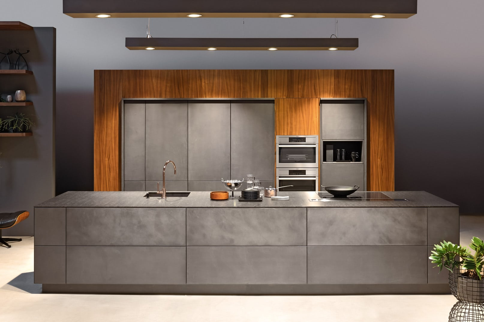 Ein absolut starkes Designhighlight zur grauen Steinoberfläche dieser Küche ist die Vertafelung aus Kirschholz als Kontrast. (Foto: KH Systemmöbel/ Beste Küchen)