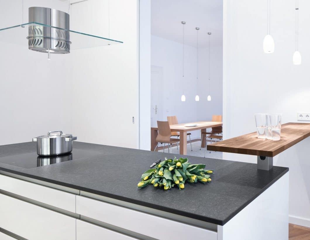Eine stimmige Küchenplanung gelingt mit den richtigen Materialien (hier: Arbeitsplatte aus Nero-Assoluto-Stein, Theke aus geöltem Nussbaum-Holz) und einer perfekt abgestimmten Lichtplanung, die die Hotspots in Szene setzt. (Foto: selektionD)