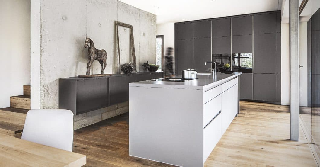 Holzbetonte Wärme und eleganter Purismus werden hier durch warm-graue Küchenfronten vermittelt. (Foto: selektionD)