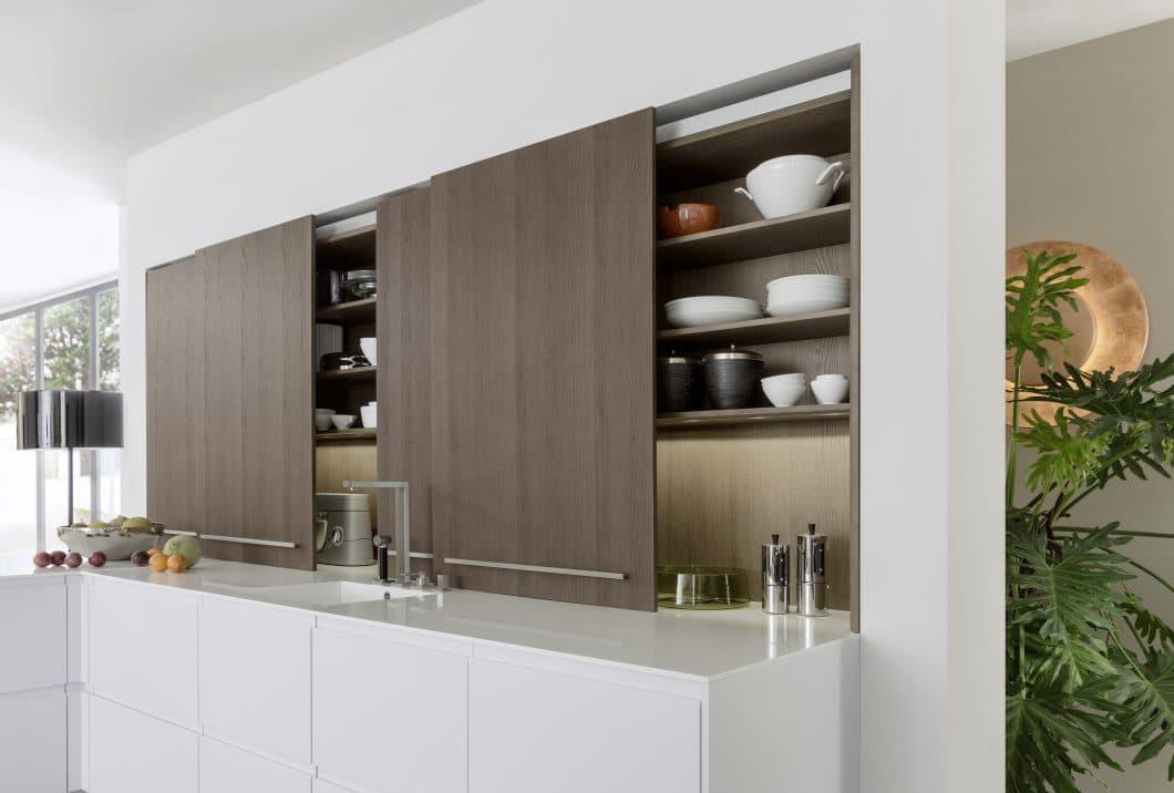 """Auch als Schiebetür in """"Esche Madeira"""" bietet LEICHT eine clevere Stauraumlösung für versteckte Küchen bei seiner Topos-Kollektion an. (Foto: LEICHT)"""