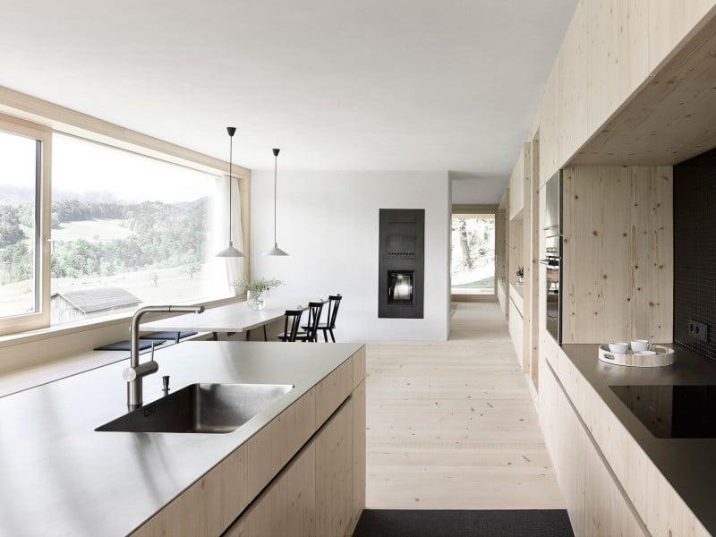 Eine helle aufgeräumte küche aus fichtenholz und eine puristische sitzecke vor einem panorama