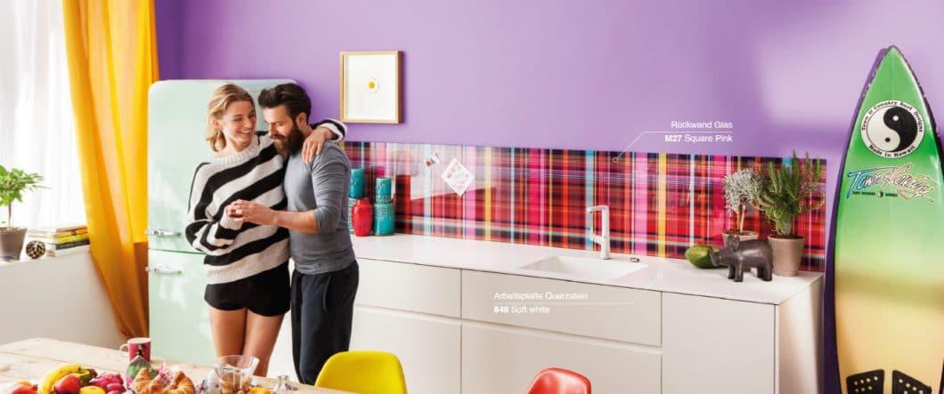 """Manche mögen's bunt: Lechner kombiniert eine zurückhaltende Arbeitsplatte aus Quarzstein mit der fröhlich-grellen Glasrückwand """"Square Pink"""". Definitiv ein Hingucker beim Mix & Match! (Foto: Lechner)"""