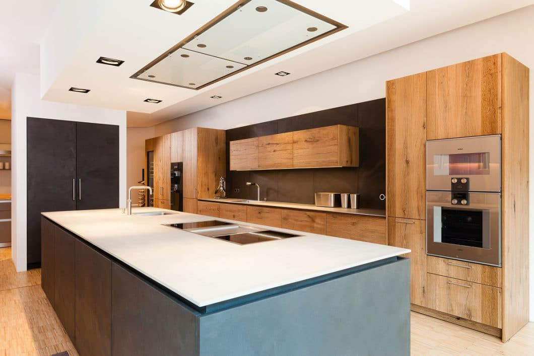 Beim Industrial Style wird Beton in der Küche häufig mit warmen Holztönen, Metall-Accessoires und mildem Licht kombiniert. (Foto: Lang Küchen & Accessoires)