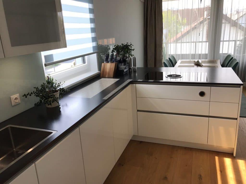 Weiße Küche mit schwarzer Arbeitsplatte ...