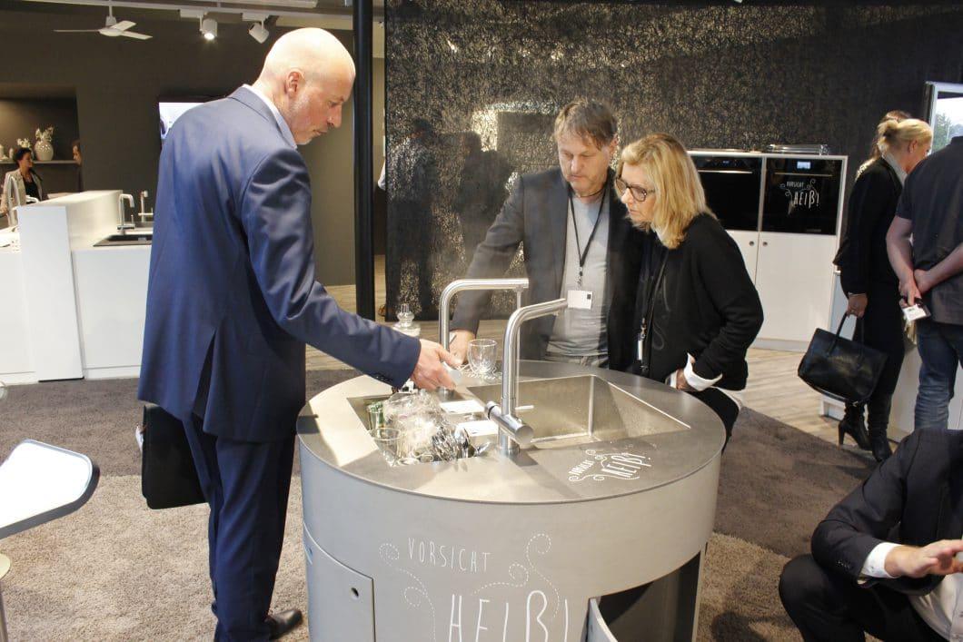 """Interessierte Besucher testen die Armatur Mondial mit ihren kochend-heißen Funktionen auf der Küchenmeile im """"house4kitchen"""". (Foto: Scheffer)"""