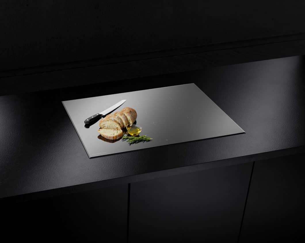 Das Designkochfeld ist auch in Schwarz und Grau erhältlich. Mit der Abdeckklappe aus Schwarzglas wird die Muldenlüftung in diesem Fall komplett unsichtbar - ein Traum für alle Ästheten. (Foto: Küppersbusch)