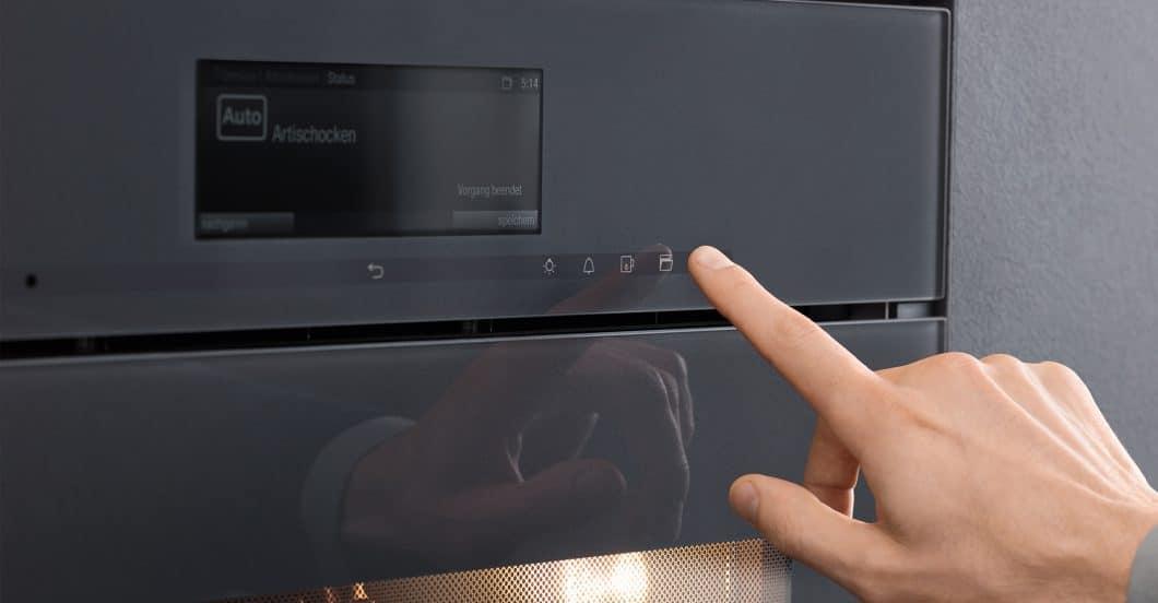 """Ein sanfter Knopfdruck genügt, und schon fährt sich die Backofentür dank der """"SoftOpen""""-Funktion nahezu geräuschlos aus. (Foto: Miele)"""