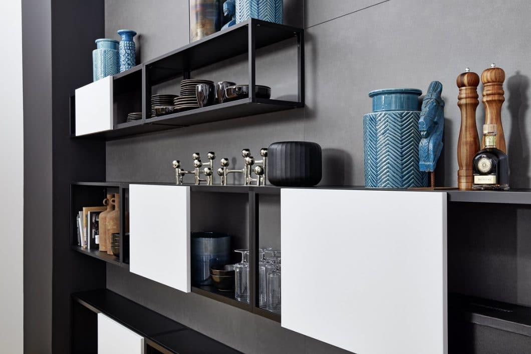 Die 2 neuen Metallfronten werden in verschiedenen Küchenmodellen vorgestellt. Bei diesem Modell greift der Wandschrank CUBE die dunkle Kücheninsel aus Blaustahl auf und kombiniert sie mit wohnlichen Regalelementen in Arctic-Weiss. (Foto: Nolte Küchen)