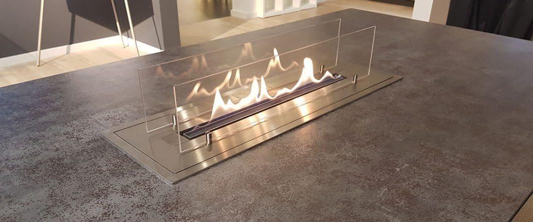 Die Glaspaneele rund um den Tischkamin sorgen für Sicherheit und reflektieren die tanzenden Flammen. Dank der verpuffungsfreien Zündung des Brenners ist der Tischkamin absolut unbedenklich einsetzbar. (Foto: Rosskopf + Partner)