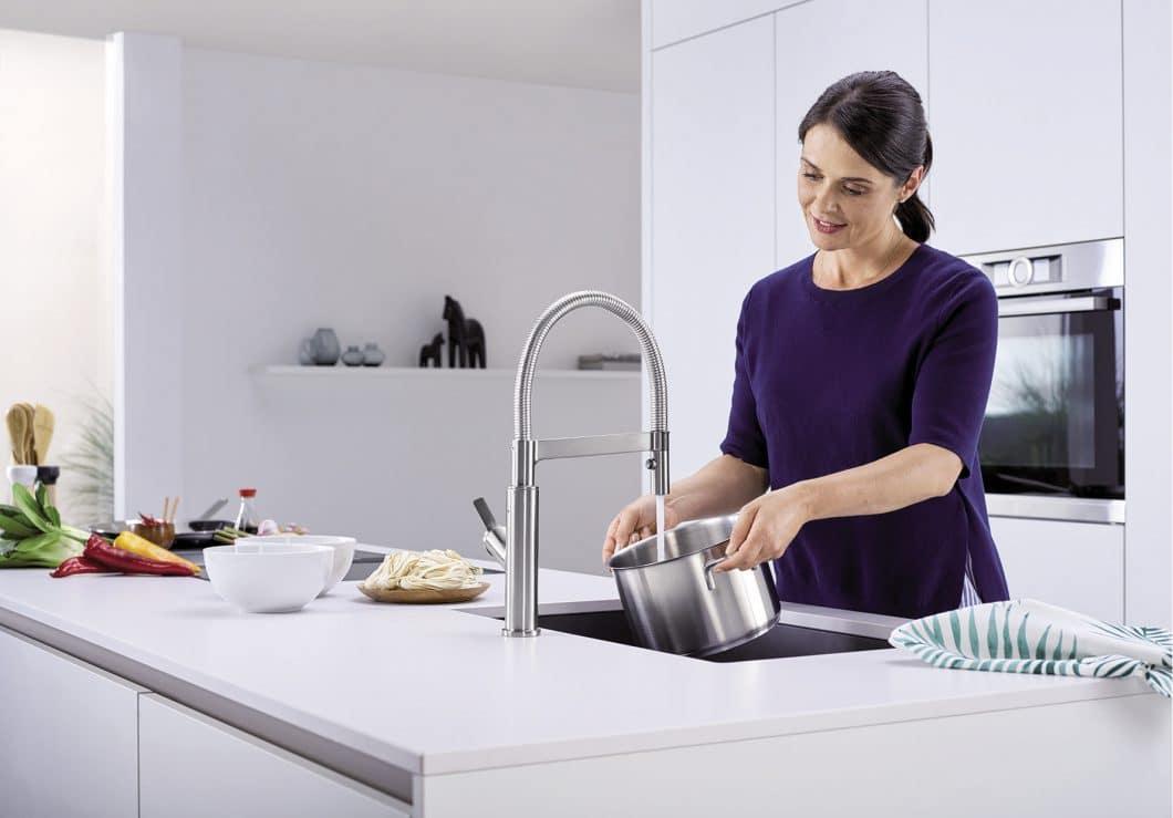Wer kennt nicht diese Art von Arbeiten in der Küche, bei denen wahlweise keine Hand frei - wie hier beim Topf befüllen - oder aber schmutzig, z.B. nach dem Schneiden von Lebensmittel ist? BLANCO SOLENTA-S schafft Abhilfe per Nahdetektion. (Foto: BLANCO)