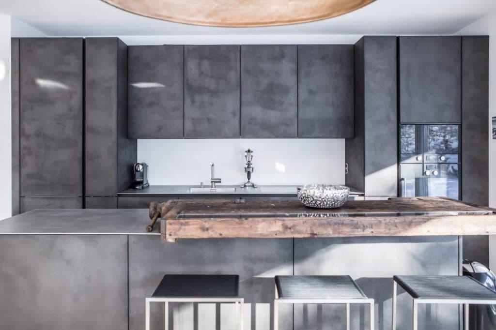 Man traut sich 2018 in der Küche mehr Individualität zu: Handgespachelte Betonfronten oder alte Hobelbänke, die abgeschliffen zu neuen Küchenbars umfunktioniert werden, geben der Küche eine persönliche Note. (Foto: Dross&Schaffer München West)
