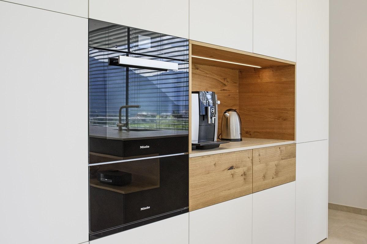 Die weiße Gerätewand in Lack matt wird durch das wiederkehrende Element aus Holz in Alpineiche Natur aufgelockert. (Foto: Couchzone)