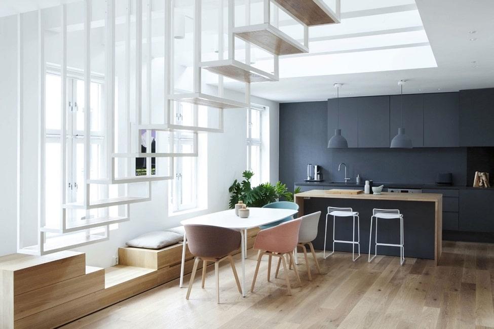 Dieser entwurf zeigt die sitzgruppe in buntem kontrast zum einheitlich dunkelblauen grifflosen küchenraum dennoch