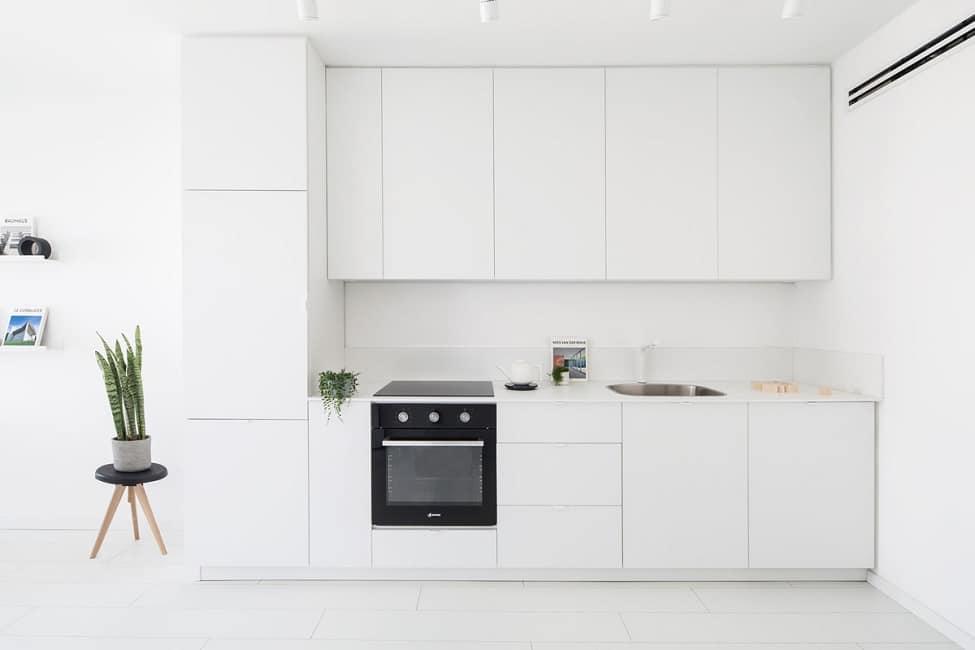 Wer zurückhaltende akzente in einer minimalistischen weißen küche setzen will kann zu farbigen einbaugeräten und grünpflanzen greifen