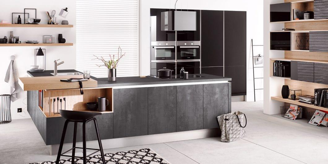 Moderne Küche mit hellen Holzelementen und einer eleganten Kochinsel aus dunklem Beton. (Foto: Häcker)
