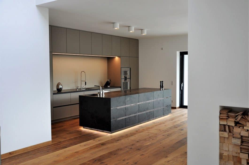 Das Licht in der Küche ist ein bedeutender Faktor in der Küchenplanung, der von Anfang an in eine ganzheitliche Betrachtung einbezogen werden sollte. Dieses Licht lässt den Küchenblock beispielsweise nahezu schweben und verleiht ihm dadurch eine noch majestätischere Ausstrahlung. (Foto: Dross & Schaffer Ludwig 6)