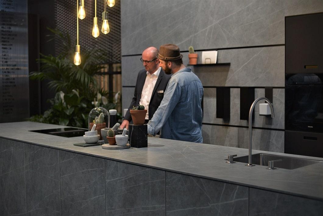 next125 präsentierte sich im ansprechenden Industrial Style: Glühlampen, Pflanzen und lässige Hängeregale treffen auf hochwertige Keramik-Arbeitsplatten und eine puristische Verarbeitung auf der EuroCucina 2018. (Foto: Sophie Engelhard)