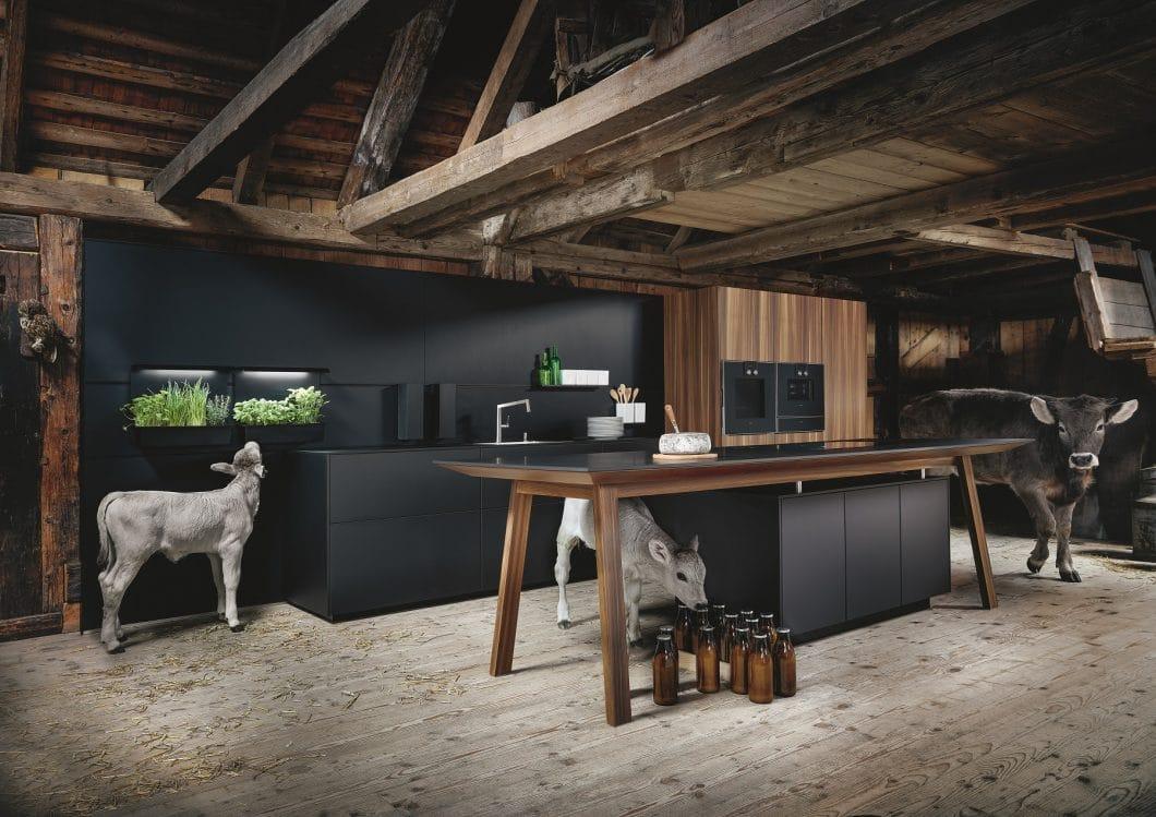 Die onxyschwarze Fenixküche bildet einen atmosphärischen Kontrast zum Lärchenholz und dem Balkengerüst der alten Mühle. (Foto: next125)