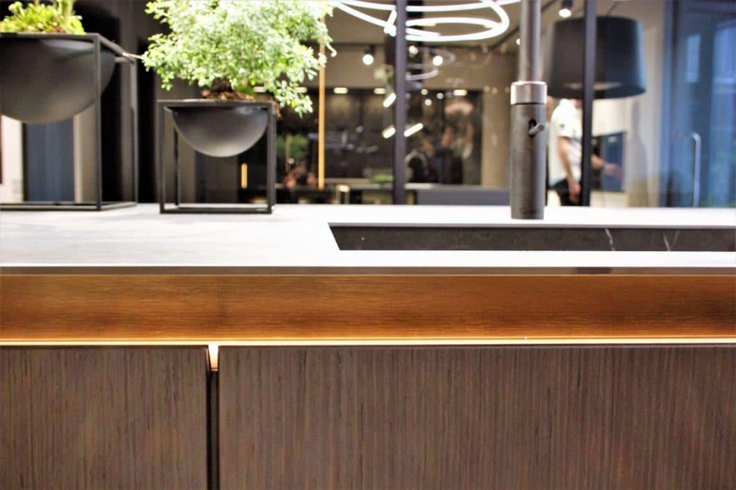 Die abgeschrägte und mit einem LED-Band besetzte Griffleiste wahrt den Anschein einer grifflosen Küche, unterstützt aber durch eine griffige Haptik das leichte Aufziehen der Schubladen und Auszüge. (Foto: Susanne Scheffer)