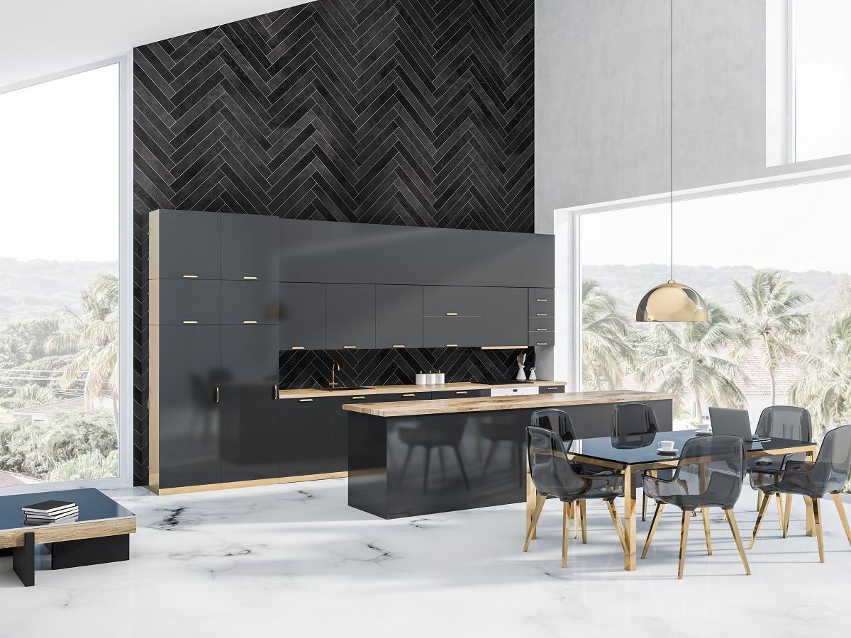 Dieser pompöse Essbereich mit einer Wand in dunkler Fischgrätenoptik, einer Küche mit anthrazitfarbenen Hochglanzfronten, transparenten Stühlen sowie goldenen Akzenten, die sich durch den gesamten Raum ziehen, wirkt eindrucksvoll und künstlerisch. (Foto: Stock Adobe/denisismagilov)