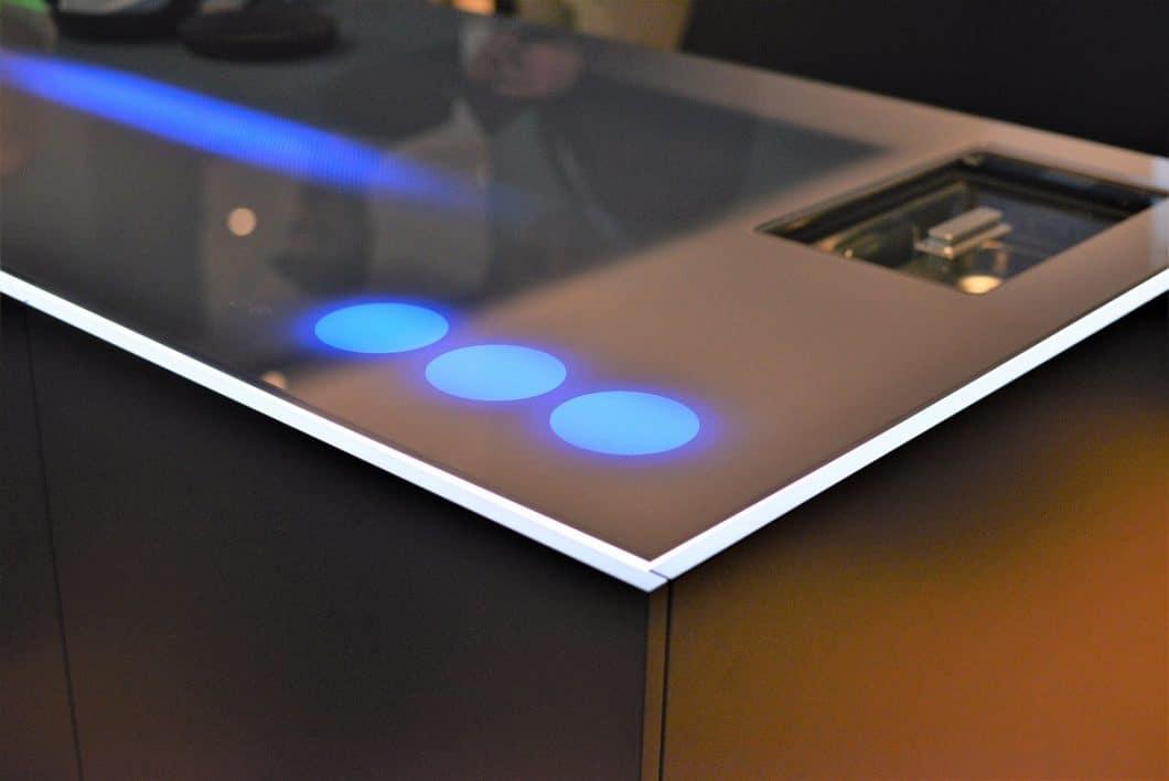 Neongelb, Grün oder doch ein tiefes, entspannendes Blau? Die Think Next By Franke-Kücheninsel kann dank smarter LED-Beleuchtung in stimmungsvolles Partylicht getaucht werden - und Drinks besonders repräsentativ platzieren. (Foto: Sophie Engelhard)