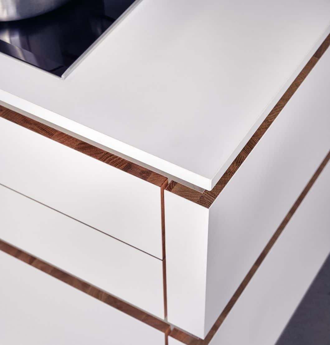 Das Besondere an Solid: von außen mit weiß-minimalistischen Fronten ausgestattet, offenbart sich schräg seitlich das Spiel aus den fein strukturierten Massivholzkanten, die die Schubladen und Auszüge umlaufen. (Foto: LEICHT)